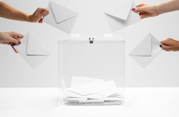 People holding white envelopes ready to put them into ballot box Premium Photo