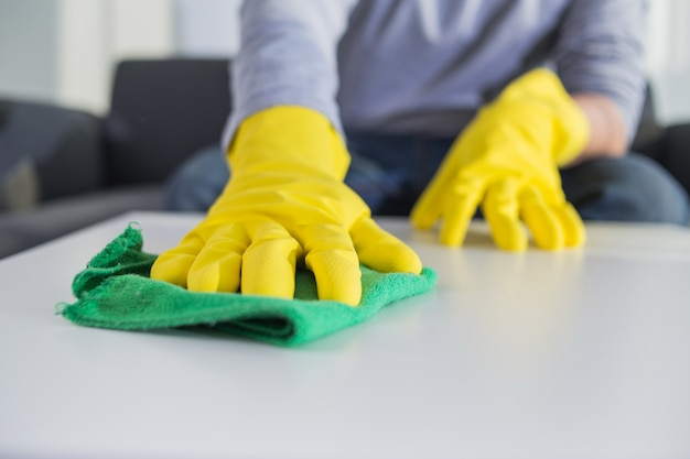 people, housework and housekeeping concept - close up of man hands cleaning table with cloth at home Free Photo