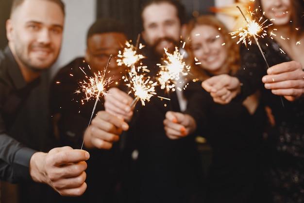 Люди в украшениях christman. мужчина в черном костюме. групповое празднование нового года. люди с бенгальскими огнями. Бесплатные Фотографии