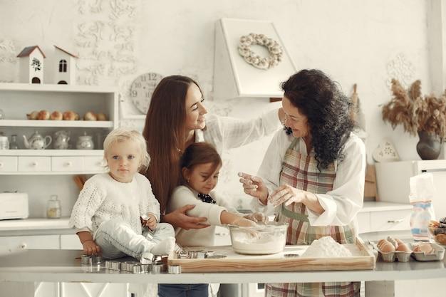 부엌에있는 사람들. 가족은 케이크를 준비합니다. 딸과 손자와 성인 여자입니다. 무료 사진