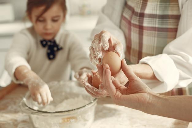 부엌에있는 사람들. 작은 딸과 함께 할머니입니다. 성인 여자는 요리하는 어린 소녀를 가르칩니다. 무료 사진