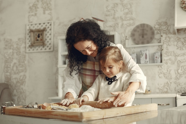 台所の人々。小さな娘を持つ祖母。大人の女性は小さな女の子に料理を教えます。 無料写真