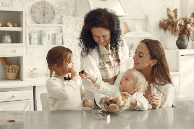 台所の人々。小さな孫を持つ祖母。子供たちはクッキーを食べます。 無料写真