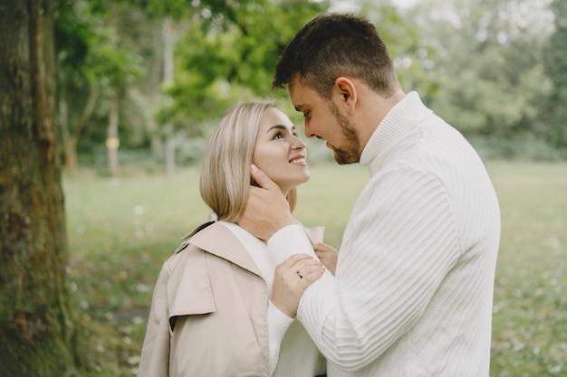 공원에있는 사람들. 갈색 코트에 여자입니다. 흰색 스웨터에 남자. 무료 사진