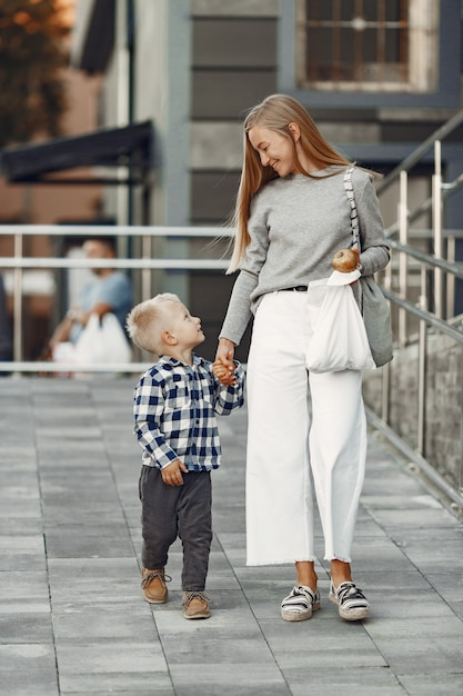 Люди в летнем городе. мать с сыном. женщина в сером свитере. Бесплатные Фотографии