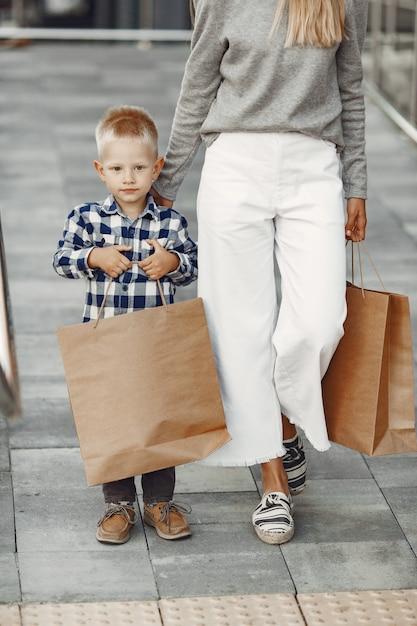 夏の街の人々。息子と母。灰色のセーターを着た女性。 無料写真