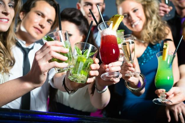 Люди в клубе или баре пьют коктейли Premium Фотографии