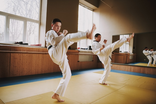 Люди в кимоно отрабатывают стойки с мма. Premium Фотографии