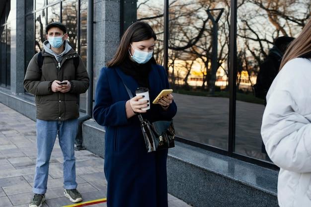 마스크를 쓰고 줄을 서있는 사람들 무료 사진