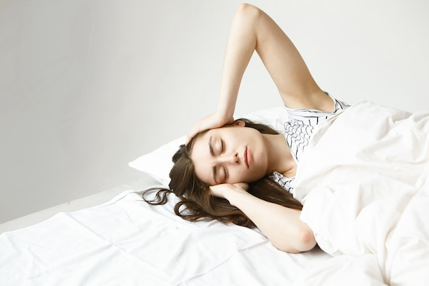 People, insomnia and sleeping disorders concept. indoor shot of beautiful sad young dark haired woman lying on white bedclothes in her room, massaging head, trying to get asleep after long working day Free Photo