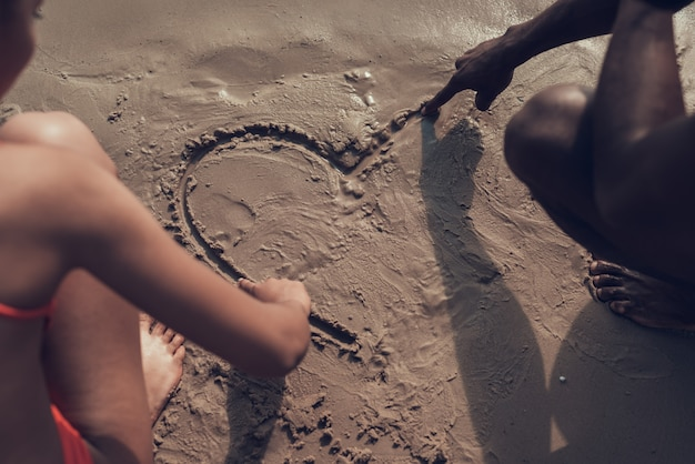 People is drawing picture of heart on sand Premium Photo