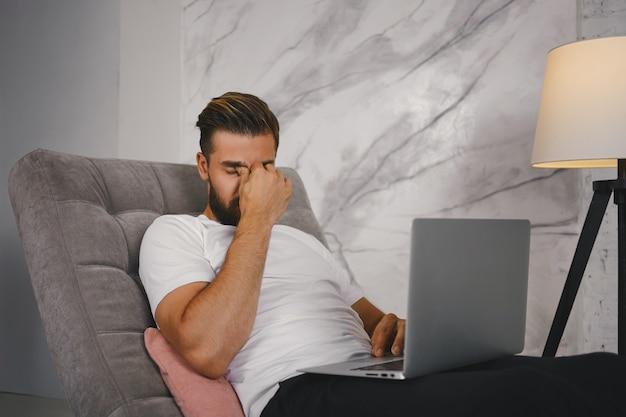 Persone lavoro, superlavoro e concetto di stanchezza. foto di elegante freelance stanco seduto sul divano con il laptop, sentendosi esausto mentre si lavora a un progetto urgente a tarda notte, massaggiando il ponte nasale Foto Gratuite