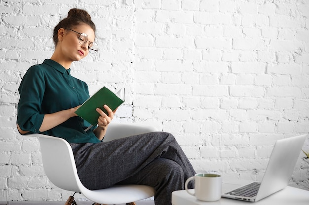 People, job, technology and modern lifestyle concept. portrait of concentrated serious businesswoman in stylish eyewear working remotely at cafe, writing in diary, sitting with laptop and cup Free Photo