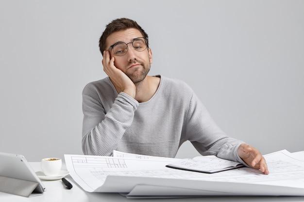 Persone, lavoro, concetto noioso e superlavoro. ingegnere maschio assonnato annoiato che lavora alle cianografie Foto Gratuite