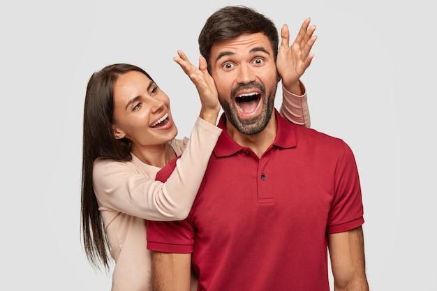 Люди, радость, приятный момент в жизни. обрадованная брюнетка европейская молодая женщина стоит рядом со своим парнем, собирается закрывать глаза и делать сюрприз, веселиться вместе, изолированные на белой стене. Бесплатные Фотографии