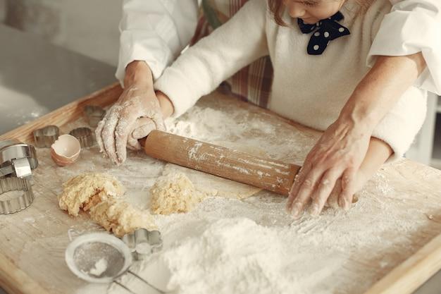 Persone in una cucina. nonna con la piccola figlia. la donna adulta insegna alla bambina a cucinare. Foto Gratuite