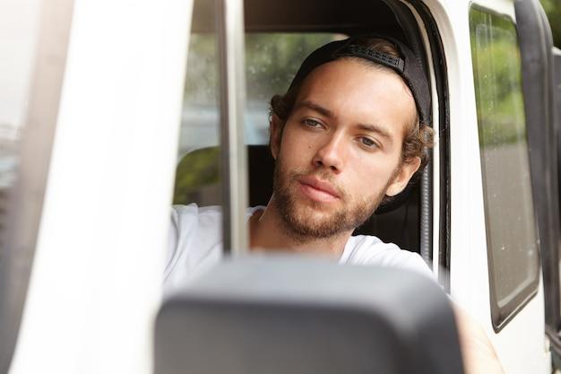 人、レジャー、冒険、極端なコンセプト。白い四輪駆動車を運転するファッショナブルな若いひげを生やした冒険家 無料写真