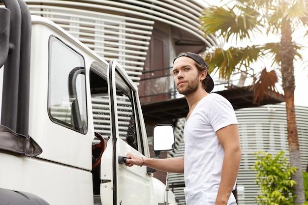 人、レジャー、ライフスタイルのコンセプトです。 tシャツと野球帽をかぶった屋外でポーズをとるファッショナブルな若い男性モデル 無料写真