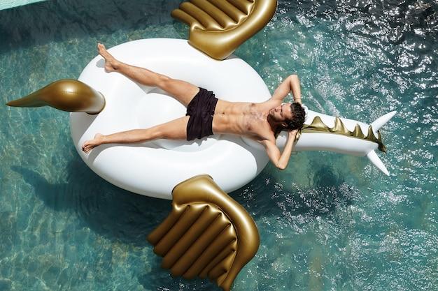 人、レジャー、休暇の概念。熱帯地方での彼の休日の自由で幸せな瞬間を楽しみながら巨大な空気ベッドに上半身裸で横たわっている魅力的な若い白人男性の屋外撮影 無料写真