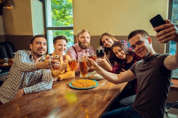 人、レジャー、友情、コミュニケーションのコンセプト。ビールを飲んだり、バーやパブでグラスをしゃべったり、チャリンという音を立てたり、携帯電話で自分撮り写真を作ったりする幸せな友達。 無料写真