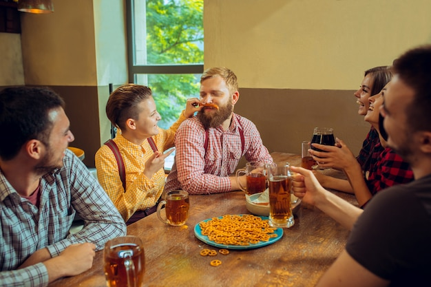 People, leisure, friendship and communication concept - happy friends drinking beer, talking and clinking glasses at bar or pub Free Photo