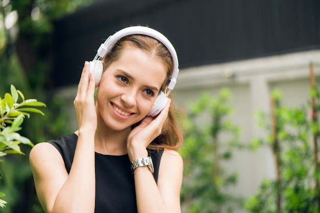 People leisure and technology concept - attractive young woman listening to music on the music player in outdoors. hipster girl enjoying the tunes in her earphones in the morning park. lens flare. Premium Photo