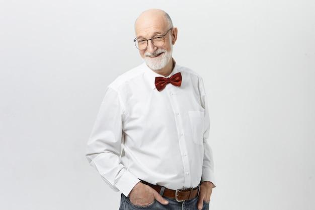 Люди, образ жизни, возраст и концепция зрелости. красивый веселый пожилой мужчина в белой рубашке, красном галстуке-бабочке, синих джинсах и очках с довольным видом, радостно улыбаясь, празднует успех Бесплатные Фотографии
