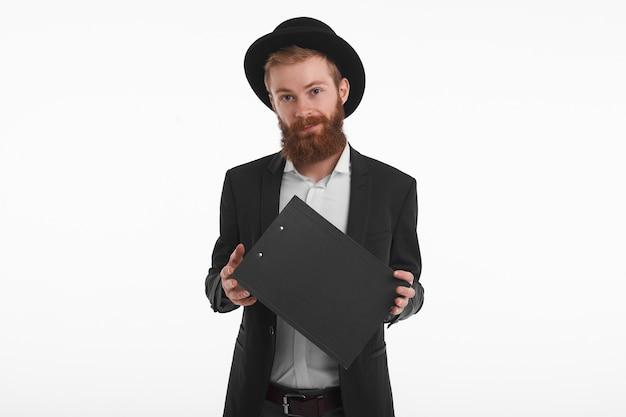 사람, 라이프 스타일 및 패션 개념. 수염을 가진 잘 생긴 젊은 백인 빨간 머리 남자의 고립 된 초상화, 검은 양복과 모자를 쓰고, 클립 보드를 들고 웃고 무료 사진