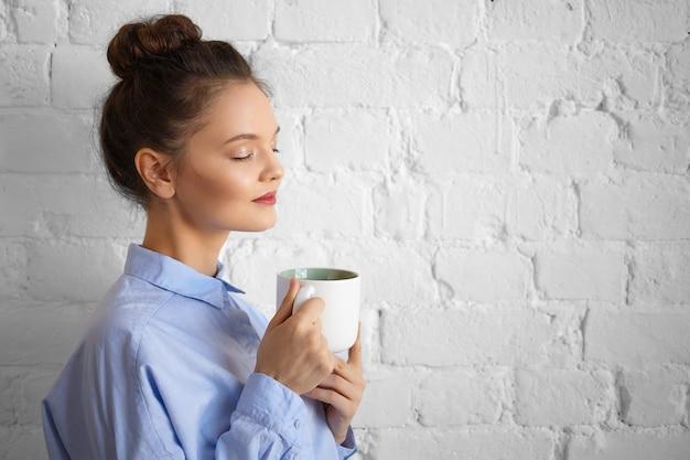 Люди, образ жизни, напитки, еда, отдых и концепция релаксации. крытый снимок красивой великолепной молодой женщины-менеджера в стильной формальной рубашке, держащей чашку, наслаждающейся утренним кофе с закрытыми глазами Бесплатные Фотографии