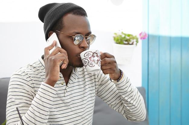 人、ライフスタイル、コミュニケーション、現代の技術コンセプト。お茶やコーヒーを飲みながら電話で話している魅力的な若いアフロアメリカン学生 無料写真