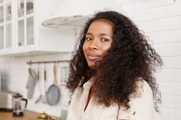 人、ライフスタイル、料理、食べ物のコンセプト。仕事から夫を待っている巻き毛のかわいいスタイリッシュな若い暗い肌の主婦の屋内ショット、キッチンで夕食を作りに行く、見て 無料写真