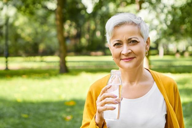 Persone, stile di vita, abitudini sane e concetto di ristoro. immagine esterna della femmina europea anziana energica felice con la bottiglia della tenuta del taglio di capelli corto, godendo dell'acqua potabile fresca sulla giornata di sole calda Foto Gratuite