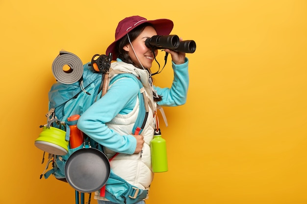 People, lifestyle, holiday, tourism concept. cheerful female tourist observes something in binoculars, stands with backpack, wears casual active wear Free Photo