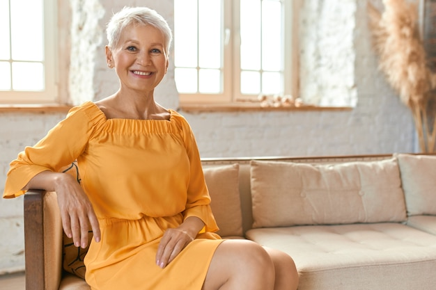 People, lifestyle, leisure, retirement and relaxation. indoor shot of beautiful fashionable european female pensioner in yellow dress sitting comfortably on couch in living room, smiling happily Free Photo