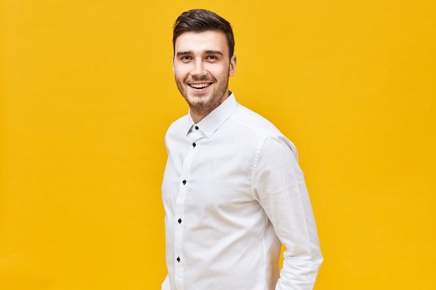 Люди, образ жизни, успех и концепция уверенности. веселый привлекательный молодой кавказский мужчина в формальной стильной одежде позирует изолированно с уверенной широкой улыбкой Бесплатные Фотографии
