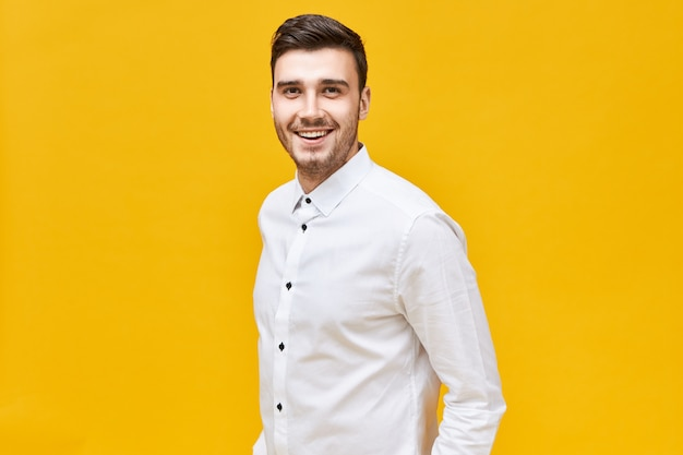 Persone, stile di vita, successo e concetto di fiducia. allegro attraente giovane maschio caucasico indossando abiti eleganti formali in posa isolato con ampio sorriso sicuro Foto Gratuite