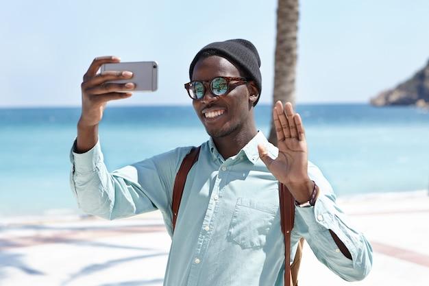 人、ライフスタイル、旅行、観光、そして現代のテクノロジー。スタイリッシュな色合いと幸せな笑顔と青い海に対してこんにちはジェスチャーでselfieのポーズをとる帽子の魅力的な黒人旅行者 無料写真