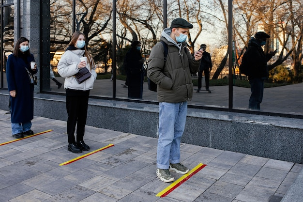 Persone in fila in attesa dietro la striscia di distanza sociale Foto Gratuite