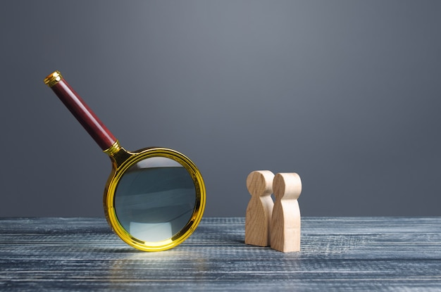 People look at a huge magnifying glass. search and analysis, analytics and study Premium Photo