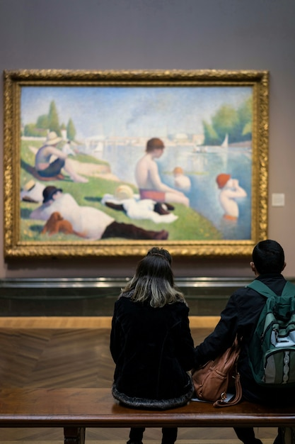 People looking a picture in the art gallery Free Photo