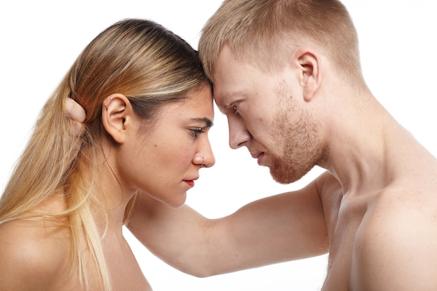 사람, 사랑, 친밀감, 섹스 및 관계 개념. 그의 매력적인 토플리스 여자 친구의 머리를 잡고 열정으로 그녀를 쳐다보고 열정적 인 Shirtless 유럽 수염 난 남자의 옆 샷 무료 사진