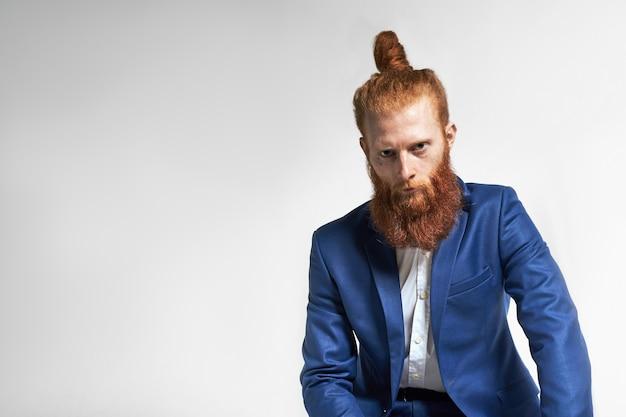사람, 남성 성, 스타일 및 패션. 텍스트 Copyspace와 회색 스튜디오 벽 배경에 포즈 두꺼운 세련된 수염을 가진 심각한 매력적인 젊은 Redhaired 남성 모델의 스튜디오 샷 무료 사진