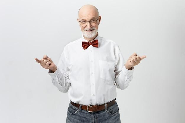 Люди, зрелый возраст, пенсия и концепция мудрости. изображение красивого жизнерадостного пожилого европейца с густой седой бородой, указывающего указательными пальцами в разные стороны и игриво улыбающегося Бесплатные Фотографии