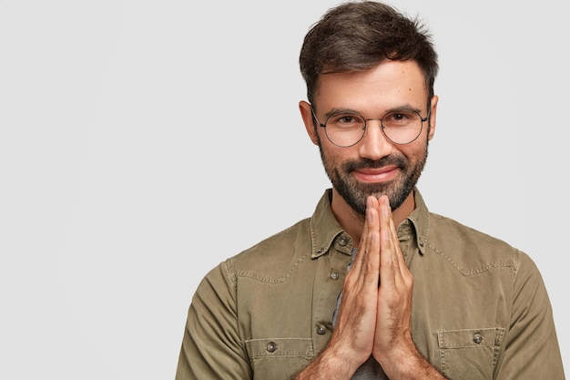 People and meditation concept. faithful pleased young european man with beard and mustache, keeps palms together, believes in something good, dressed in fashionable shirt, poses indoor alone Free Photo