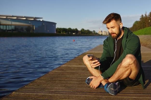 人、現代のテクノロジー、コミュニケーションのコンセプト。湖の前に足を組んで座って携帯電話を使用して音楽を聴いているスニーカーでハンサムな若い無精ひげを生やした男性のヒップスターの屋外ビュー 無料写真