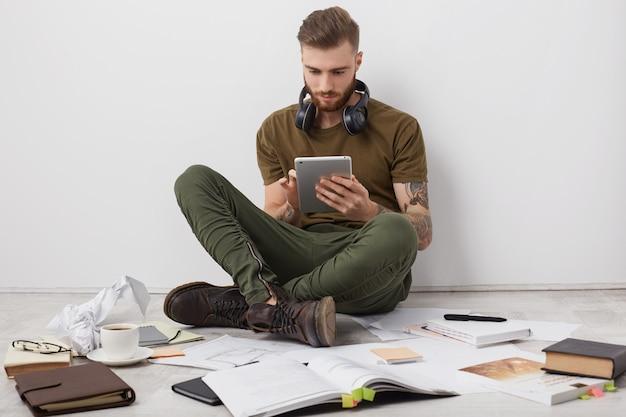 Persone, tecnologia moderna e concetto di istruzione. barbuto uomo elegante indossa stivali, si siede a gambe incrociate sul pavimento, Foto Gratuite