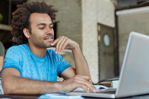 Persone, tecnologia moderna, istruzione, apprendimento e concetto di conoscenza. bello giovane afroamericano fiducioso seduto davanti al computer portatile aperto, studiando, tenendo un corso online sull'arte moderna Foto Gratuite