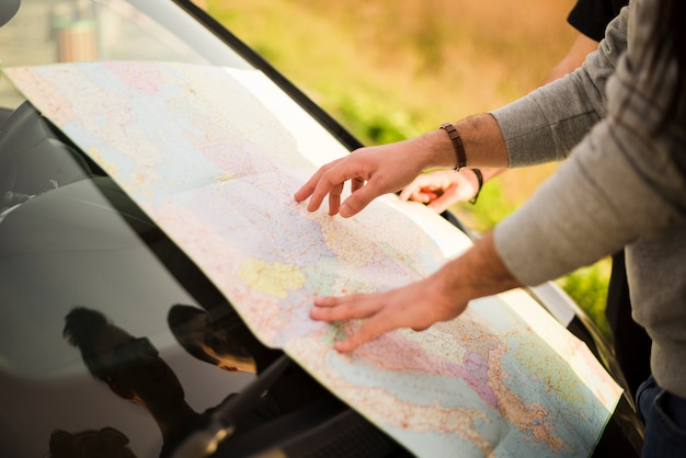 People navigating with map on a road trip Free Photo