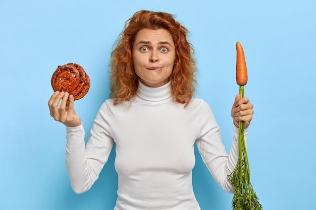 Persone, nutrizione, dieta e concetto di cibo spazzatura. donna rossa imbarazzata tiene panino fresco e gustoso e carota, sceglie tra verdura e pasticceria, indossa dolcevita bianco, sta al coperto Foto Gratuite