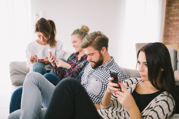 People obsessed with phones sitting on couch Free Photo